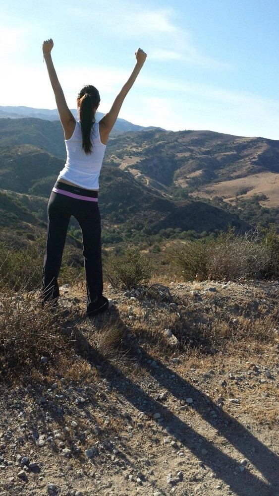 young woman standing on mountain top